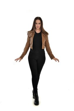 full length portrait of brunette girl wearing brown leather jacket.   standing pose on white background.