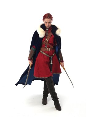full length portrait of red haired girl wearing fantasy medieval costume, standing pose on studio background.
