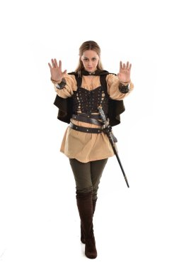 full length portrait of blonde girl wearing brown medieval warrior costume. standing pose, isolated on white studio background.