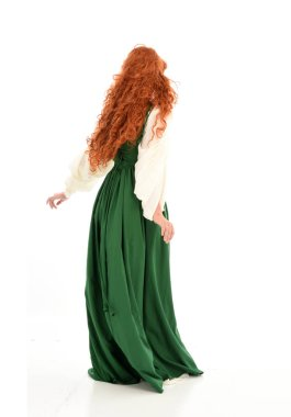 full length portrait of red haired girl wearing green medieval gown. standing pose on white studio background.
