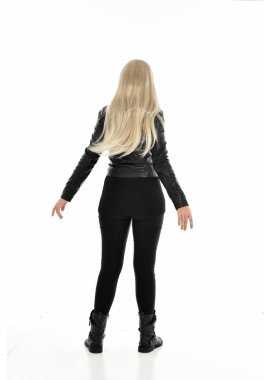 full length portrait of blonde girl wearing black leather clothes. standing pose with back to the camera. isolated on white studio background.