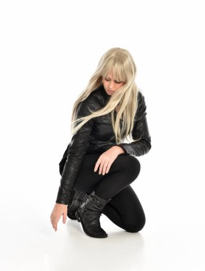full length portrait of a blonde girl wearing black leather outfit, sitting pose. isolated on white studio background.