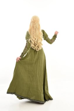 full length portrait of blonde girl wearing green medieval gown. standing pose facing away from the camera, isolated on white studio background.