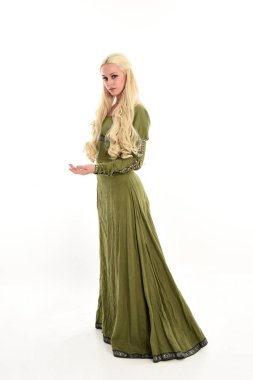 full length portrait of girl wearing green medieval gown, standing pose in side profile. isolated on white studio background.
