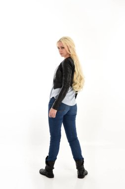 full length portrait of girl wearing simple jeans and leather jacket. standing pose, facing away from camera. isolated on white studio background.