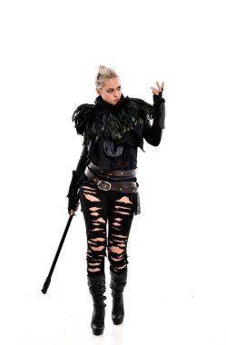 full length portrait of blonde girl wearing black torn outfit, holding a staff weapon. standing pose, isolated on white studio background.