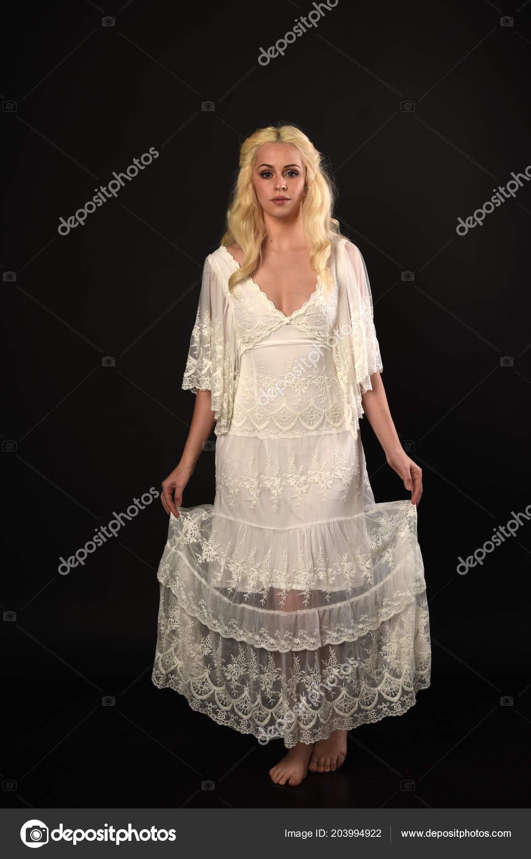 35bd575c2283 Ritratto integrale della ragazza bionda che porta vestito di pizzo bianco.  in piedi posa. sfondo nero studio– immagine stock