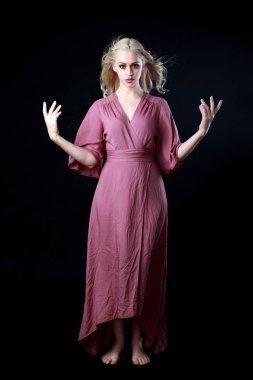 full length portrait of blonde girl wearing long purple dress. standing pose. black studio background.