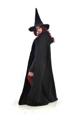 full length portrait of red haired girl wearing long black cloak, pointy hat and witch costume. standing pose, isolated on white studio background.