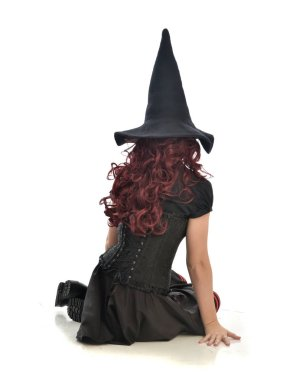 full length portrait of red haired girl wearing black witch costume and pointy hat.  seated pose, isolated on white studio background.