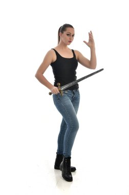 full length portrait of brunette girl wearing black single and jeans. standing pose, holding a sword. isolated on white studio background.