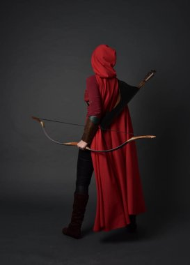 full length portrait of brunette girl wearing red medieval costume and cloak, holding a bow and arrow. standing pose on grey studio background.