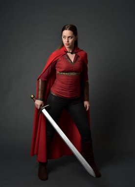 full length portrait of brunette girl wearing red medieval costume and cloak. standing pose  holding a sword on grey studio background.
