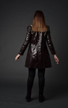 full length portrait of brunette girl wearing long leather coat and boots. standing pose with back to the camera, on grey studio background.