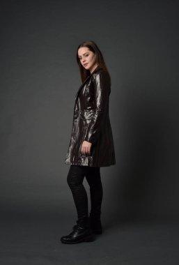 full length portrait of brunette girl wearing  red long leather jack. standing pose on grey studio background.
