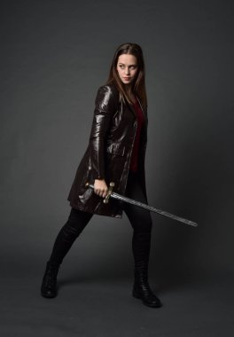 full length portrait of brunette girl wearing  red long leather jack. standing pose, holding a sword on grey studio background.