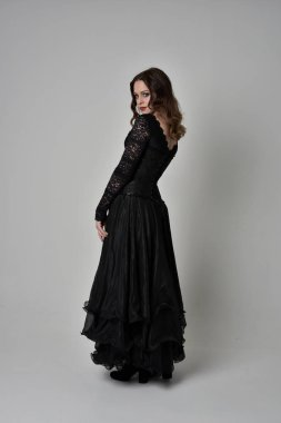 full length portrait of brunette girl wearing long black lace gown wit corset. standing pose with back to the camera. isolated on grey studio background.