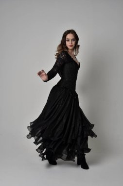 full length portrait of brunette girl wearing long black lace gown wit corset. standing pose, isolated on grey studio background.