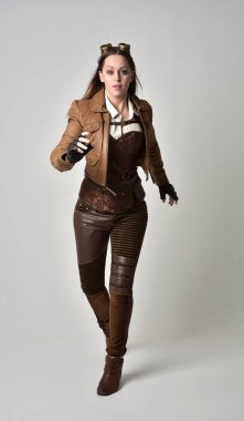 full length portrait of brunette  girl wearing brown leather steampunk outfit. standing pose on grey studio background.