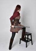 Ganztägiges Porträt eines Mädchens in mittelalterlicher Kleidung. Stehende Pose mit einem Schwert, isoliert vor grauem Studiohintergrund.