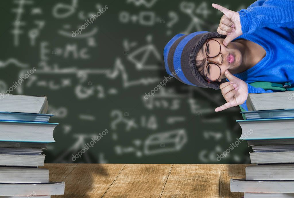 Cute male student wearing glasses, blue hat, happy smile with education, wooden desk and pile of books, and behind chalkboard concept of learning fun for children to develop well.
