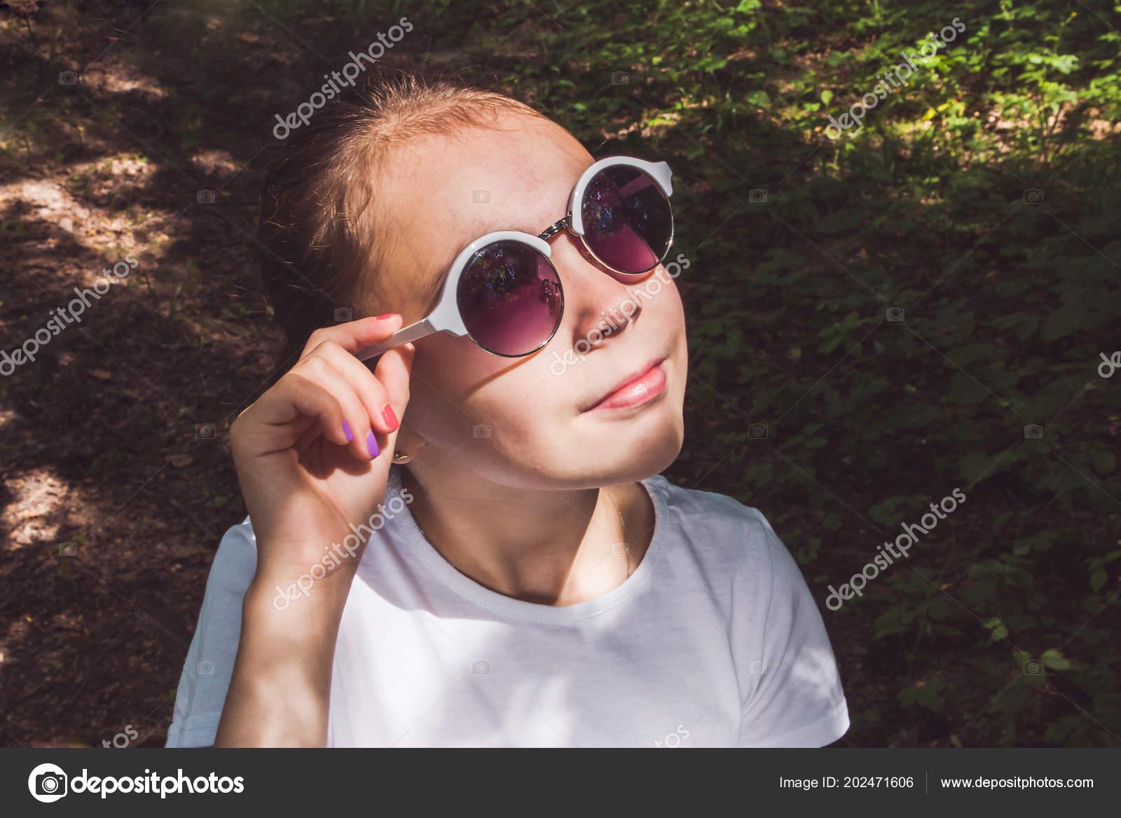 d09b61833d Bonne petite fille avec des lunettes de soleil en regardant le soleil dans  la forêt de l'été– images de stock libres de droits