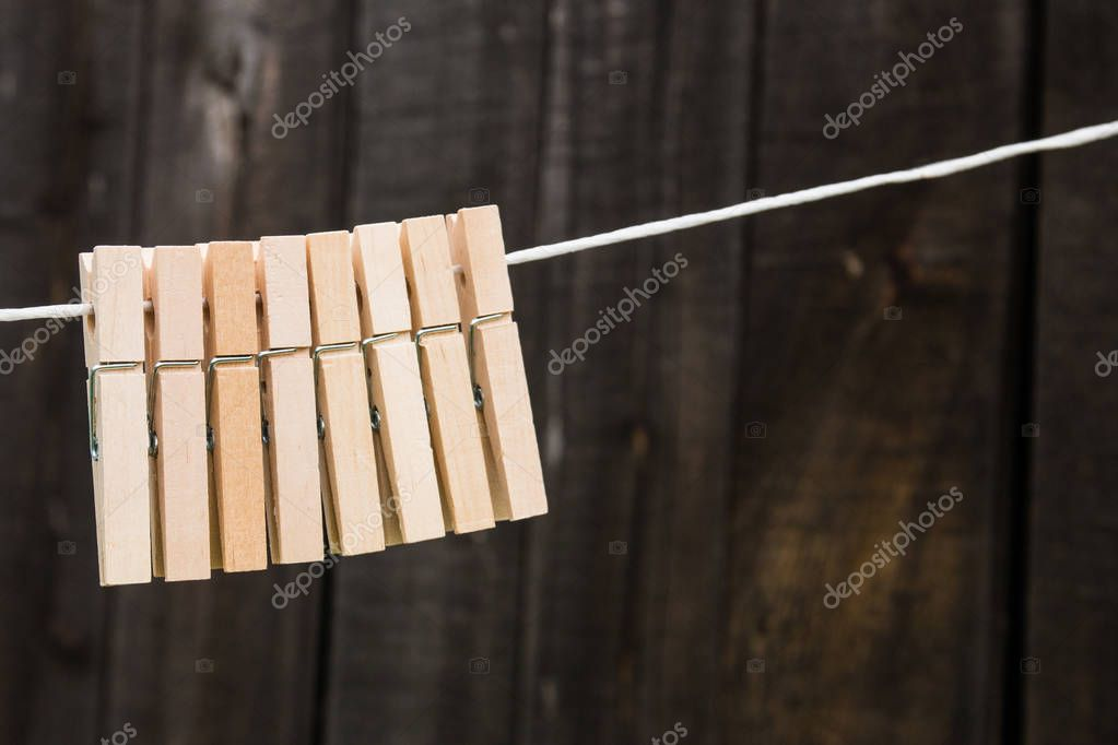 wooden clothespins hang on a rope on a wooden background.