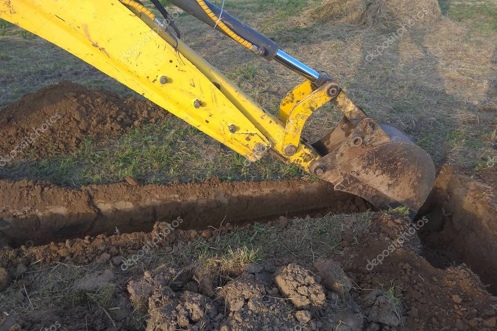 A work excavator digs a trench in a country house