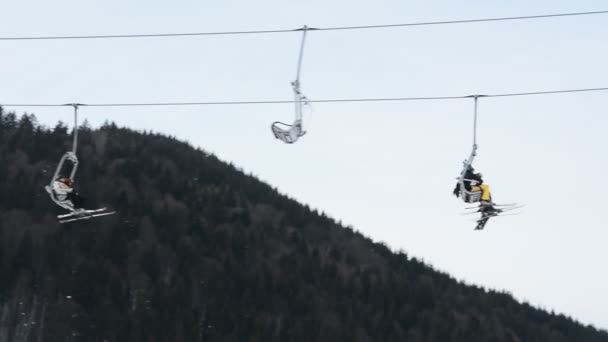 V zimním lyžařském středisku lidé lyžují a jezdí na snowboardu po zasněžených svazích. Lyžařský vlek na sněhové hoře. Zimní aktivity na lyžařském středisku