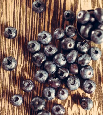 Blue berry is sweet and fragrant on a brown background.