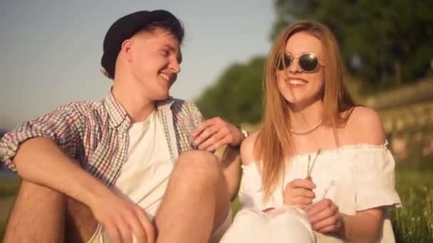 Smiling and laughing people having good time outside on summer warm day.  Dating, love, happy, smlile, lought, talking. Couple in subglasses and hat, boy have clock, they in love enjoy sunny day.