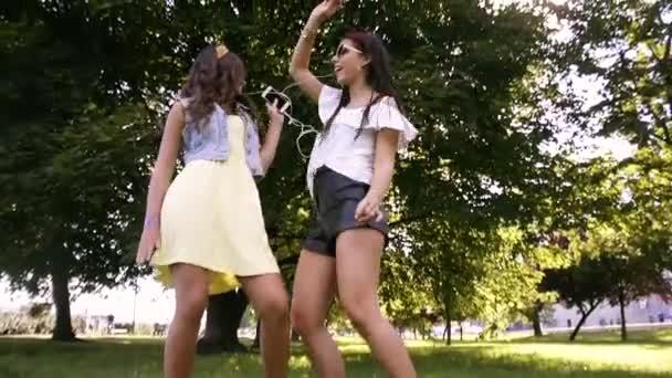 Zwei Freundinnen / Schwestern tanzen zu zweit und hören Musik. Mädchen hören über Kopfhörer Musik, singen mit und tanzen. Mädchen tanzen auf dem Gras und ruhen sich aus. Musik, Kopfhörer, Gesang, Klingeltöne