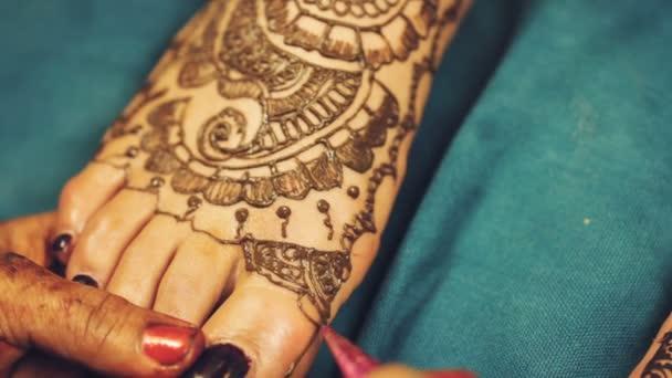 Henna művész (Mehndi) festés a tetoválás minta indiai menyasszony gyalog, az indiai esküvő napján