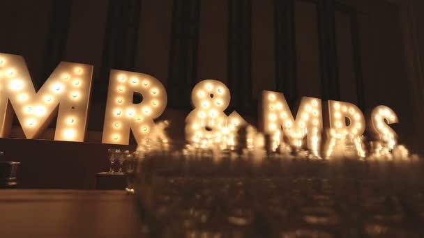 Retro-Lightbox-Theater-Stil von Text mr  mrs Dekoration auf dem Hintergrund der Hochzeitsfeier Dinner Night Party mit einer Gruppe von Weingläsern verschwommen im Vordergrund, niedriger Winkel, Dolly Schieberegler Szene.