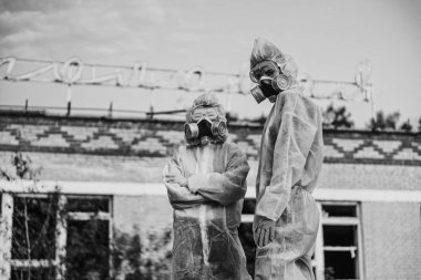 Two scientists put on a respirator and a radiation protective suit. Stern look into the camera from the abandoned territory. Coronavirus in a pandemic, COVID-19. Care about ecology in black and white photo mystical horror movie.
