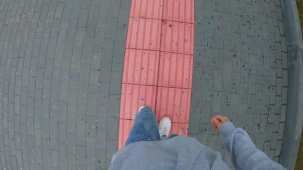 Video první osoby. Mladý muž se pohybuje po růžovém pásu s úlevou pro slepce. Cesta pro lidi, kteří ztratili zrak. Park vybavený pro tělesně postižené v Rusku.