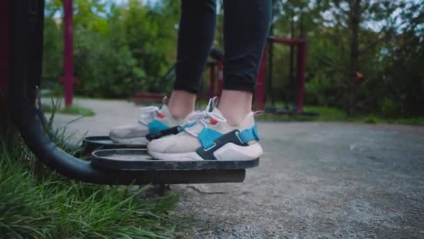 Cvič na ulici a Posilte svaly. Sportovní půda na dvoře. Ženský nohy blízko. Bezplatné cvičení v blízkosti domu.