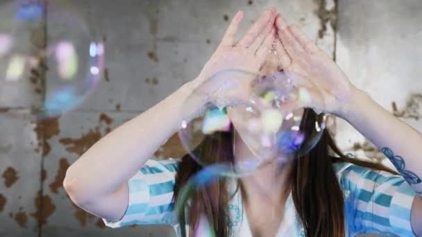 Žena foukání přes její ruce mýdlové bubliny