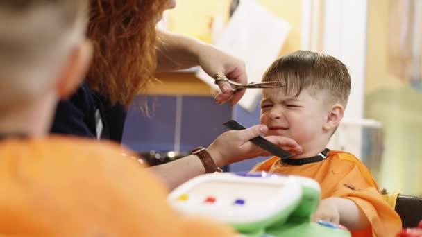 Dítě účes. Kadeřnice pracují s malým chlapcem v holičství