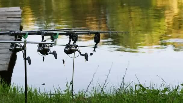Tři profesionální rybářský prut čekání na kousnutí na vodě řeky