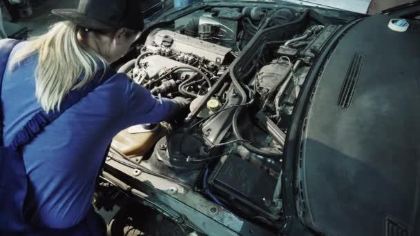 Atraktivní ženské mechanik pracuje na motor auta v garáži workshop