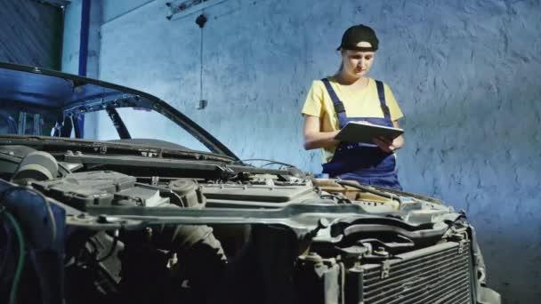 Žena mechanic používá digitální tabletu v automatické opravy garáž
