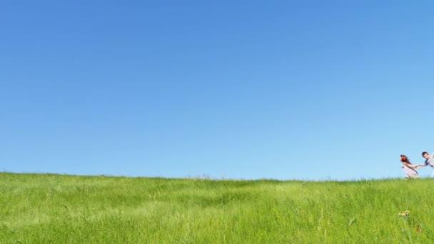 Gyermekek szaladni a domb tetején, a zöld és a repülő sárkány