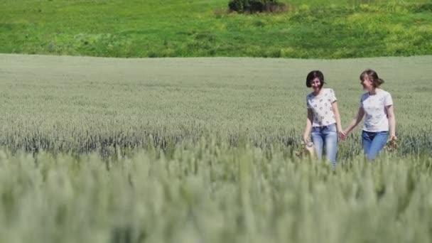 Dvě dívky, drželi se za ruce, procházky v přírodě