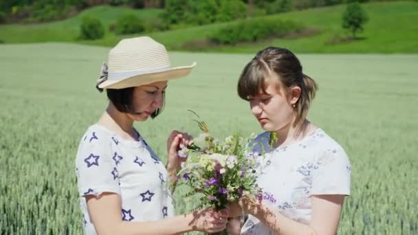 Two women are looking at a bouquet of wildflowers