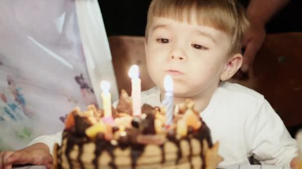 Malý chlapec tři roky staré, foukání svíčky na narozeninový dort