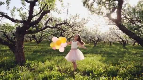 A girl of ten years playing with balloons in an apple orchard