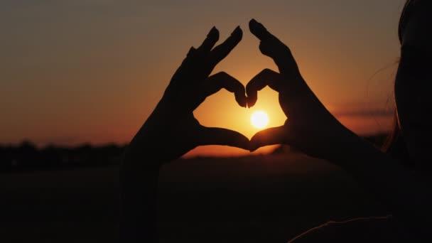 Osoba činící srdce s rukama nad přírodou západu slunce pozadí