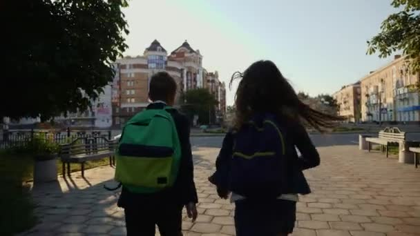 Boy and girl running with backpacks being late