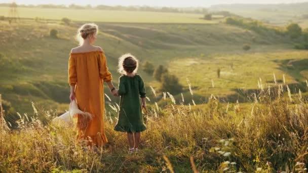 Matka s dcerou, stojící na vrcholu kopce